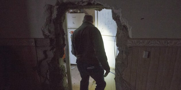 A reporter walks through a passageway opened by ISIS fighters to connect adjoining houses on Feb. 23, 2017 in Bashiqa, Iraq. The town in the Mosul district was liberated last November after being under ISIS control for two years.