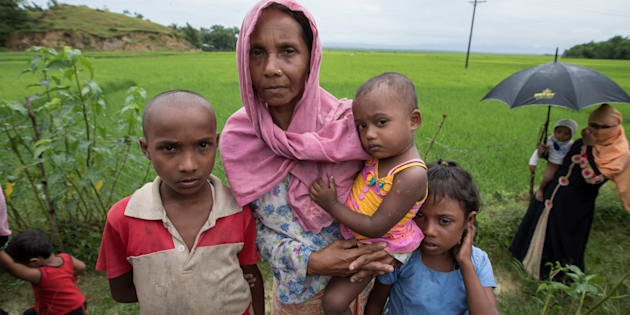 A Rohingya widow whose husband was killed in Myanmar arrives in the Bangladeshi district of Cox's Bazar with her children.