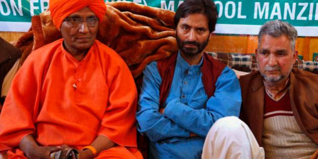 Chairman of the Jammu Kashmir Liberation Front (JKLF) Yasin Malik, center, sits for a 30-hour- long hunger strike, with social activist Swami Agnivesh, left, sitting in support in Srinagar, Indian controlled Kashmir, Saturday, April 18, 2015. Malik along with his supporters began a 30-hour hunger strike to protest India's plan to build townships for Hindus who fled a rebellion in Muslim-majority areas. (AP Photo/Mukhtar Khan)