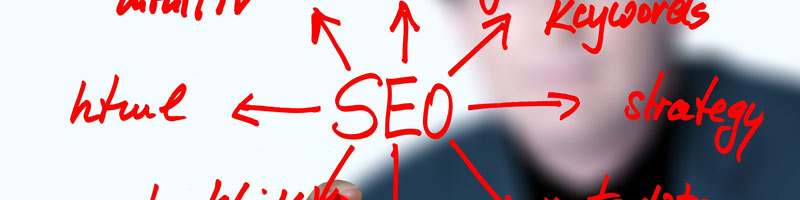 Red writing on a transparent board with SEO as the focal point with arrows pointing out to other areas of work with html and strategy clearly visible from O2 REAL 365<span srcset=