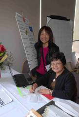 2015 New Year's Party chairperson Naomi and volunteer Doreen at the reception table (photographed by Stuart Yamashiro)
