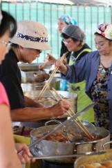 Volunteers cooking saataa andaagii at the Bazaar! Photographed by Eric Takushi.