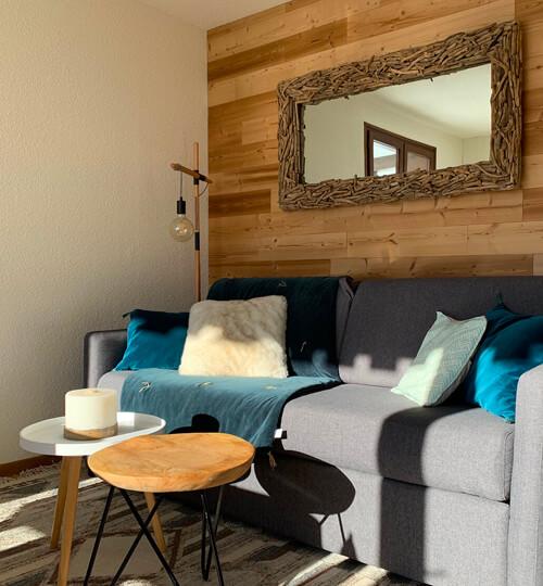 Le canapé-lit fermé dans la pièce à vivre du Chèvrefeuille avec vue sur les montagnes et le domaine skiable