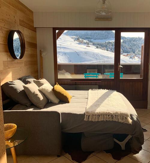 Le canapé-lit ouvert dans la pièce à vivre du kodiac avec vue sur les montagnes et le domaine skiable