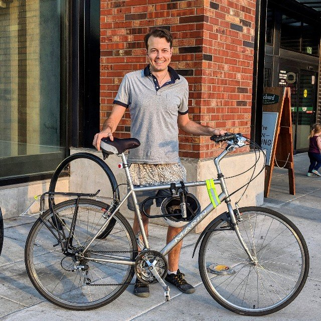 Picture of Nathan Corliss standing behind his bike which is a silver Marin bike. He's in front of a pick wall and the light is orange from a sunset.