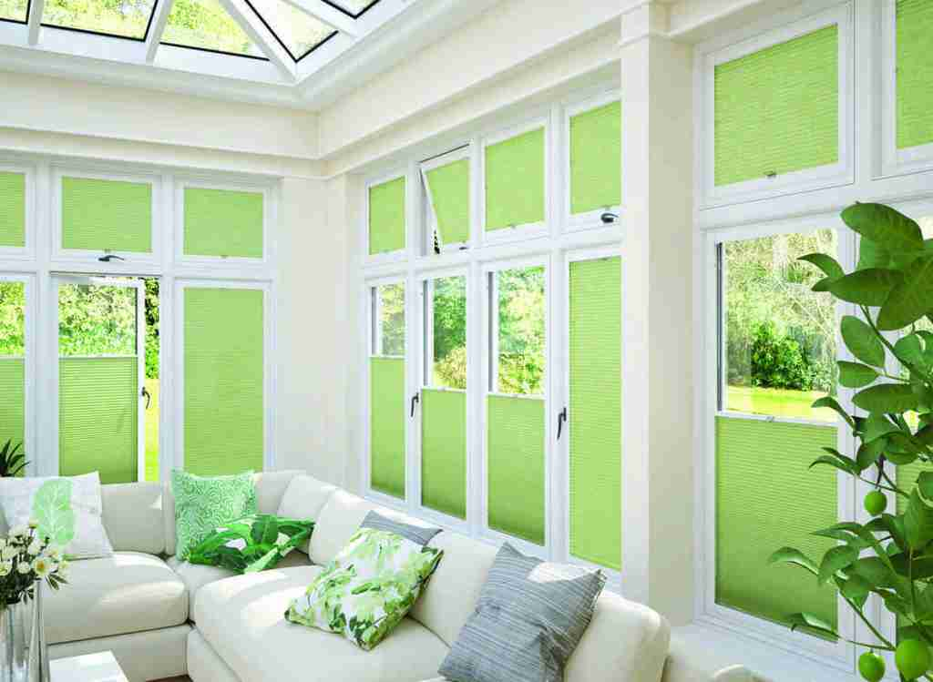 Conservatory with green perfect fit pleated blinds in the windows