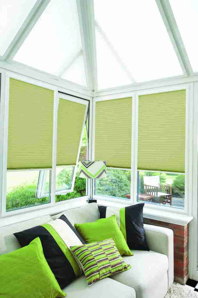 Conservatory with green perfect fit pleated blinds in the windows and white perfect fit in the roof