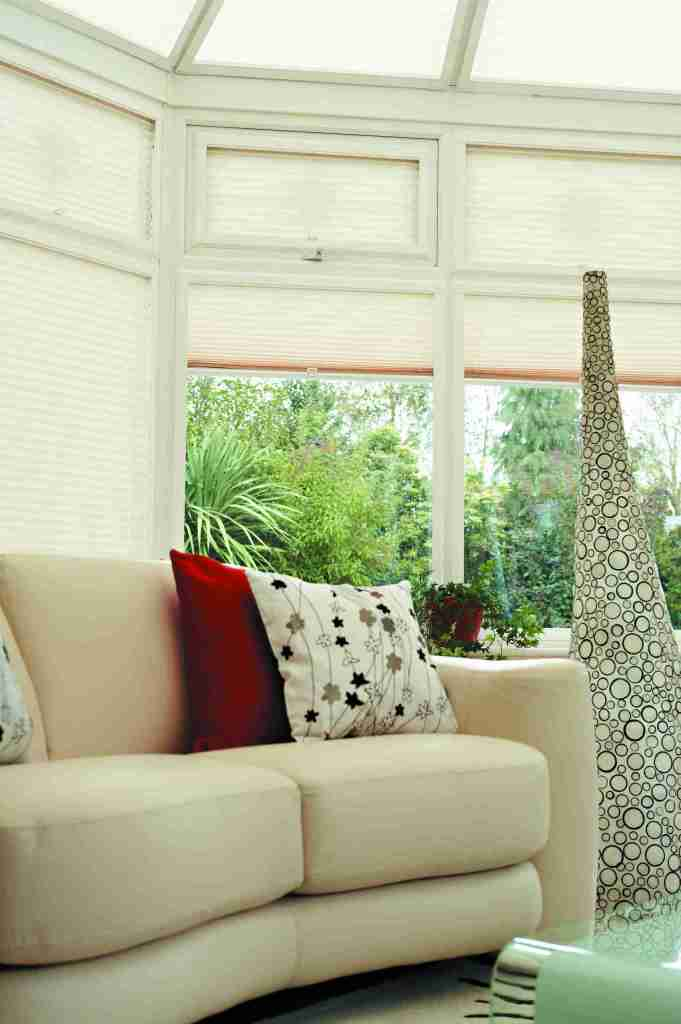 Conservatory with cream perfect fit pleated blinds in the windows