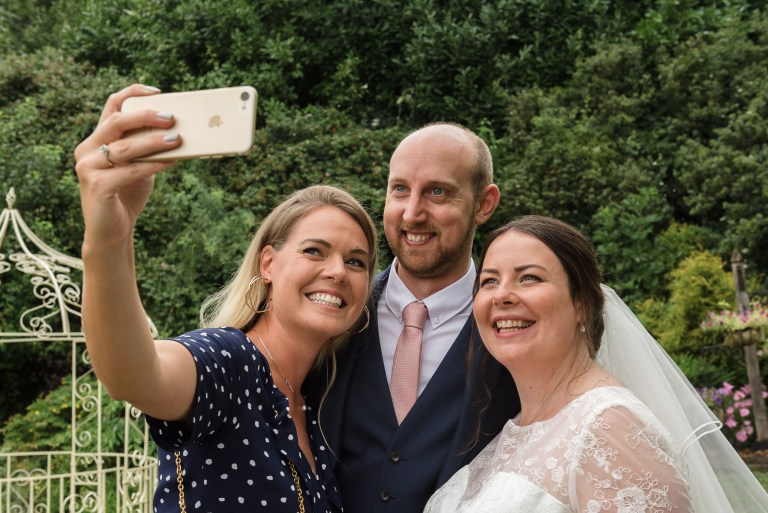 Groom having a selfie taken with wedding guests at Swallows Oast wedding venue, Ticehurst, East Sussex | Oakhouse Photography
