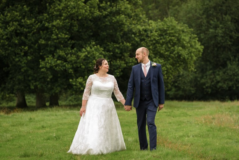 Bride and groom walking through the fields at Swallows Oast wedding venue, Ticehurst, East Sussex | Oakhouse Photography