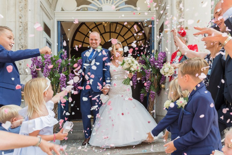 Bride and groom being showered with confetti on leaving Chelsea Old Town Hall, King's Road, London | Oakhouse Photography