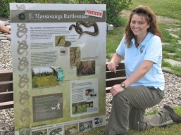 Jennifer Tucker, former director of Springfield Township Parks and Recreations, admires a new DNR rattlesnake sign in Springfield Township.