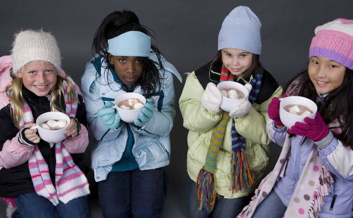 Four young girls bundled up in winter coats drinking hot chocolate.