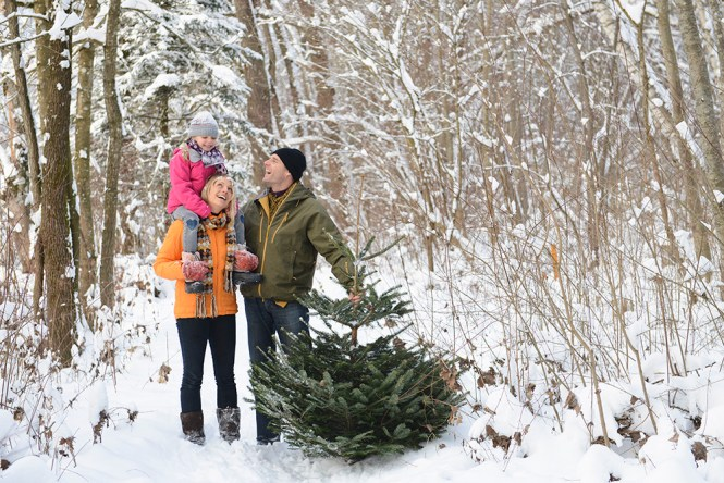 Family stands beside a Christmas tree in a forest.