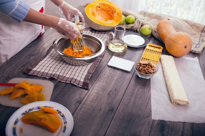 Woman in kitchen making prepares a pie with pumpkin, selective focus