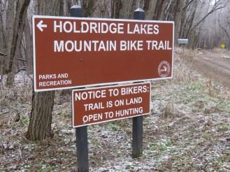 A red sign reads Holdridge Lakes Mountain Bike Trail