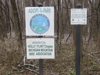 Two signs are posted in a wooded area. One says: ADOPT-A-PARK. The other says: ADOPT-A-FOREST.