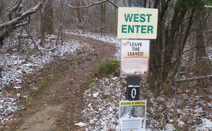 A trail winds through a heavily wooded area. A trail marker indicates the entrance to the trail.