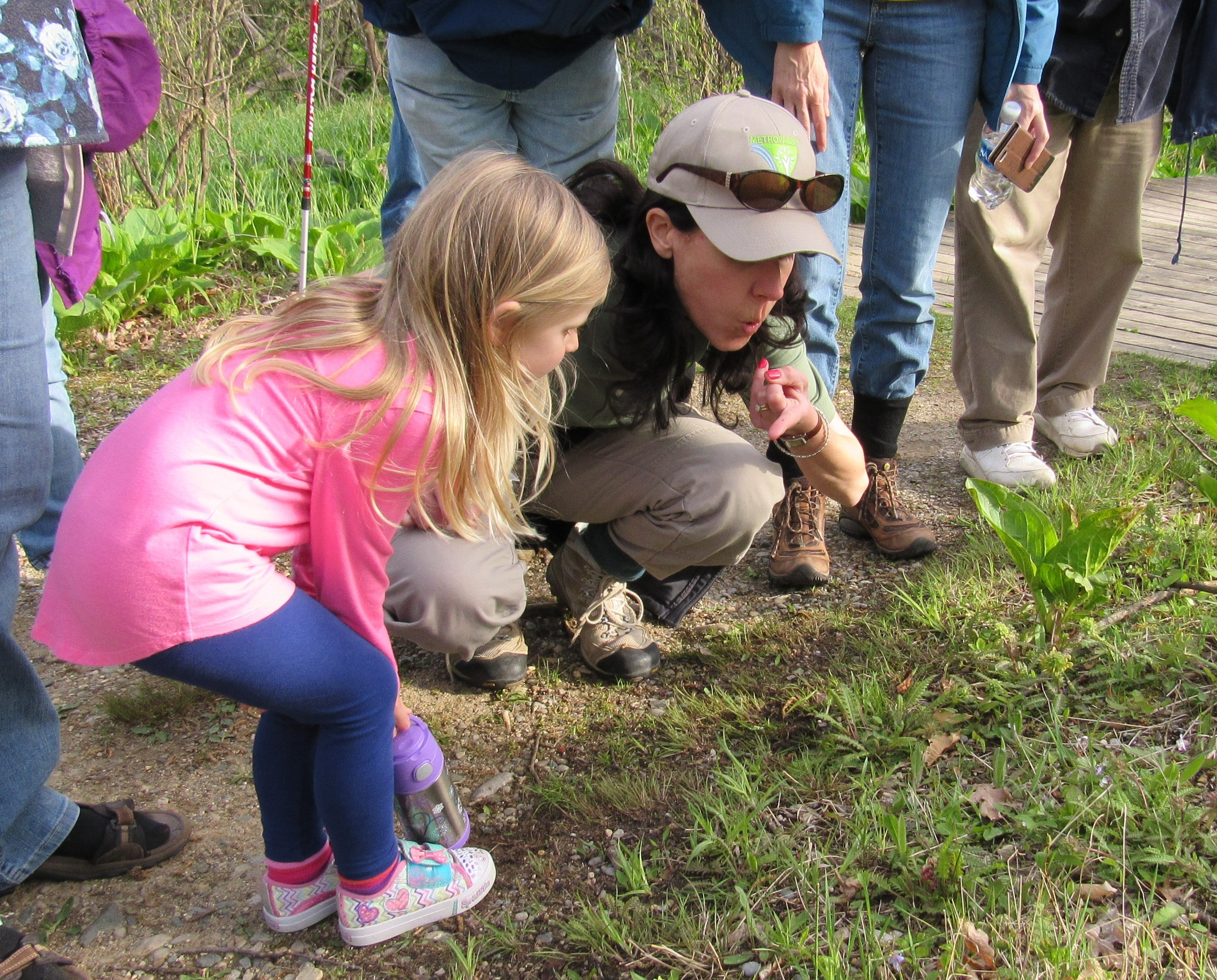 A park guide crouches down to show a young girl a bug on her finger