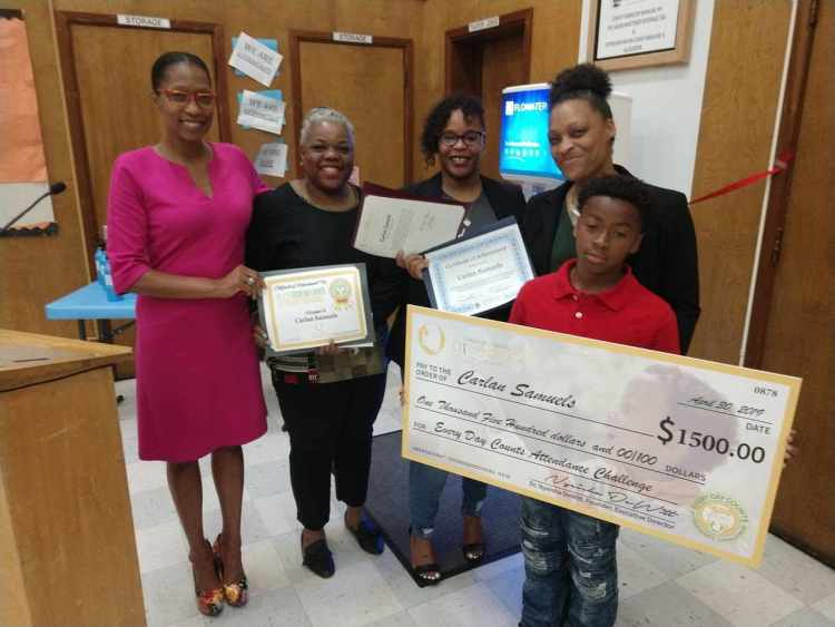 Attendance Champion Carlan Samuels, His Mother And Leaders From Oakland Natives Give Back, And The Check He Received From The Organization For His Perfect Attendance
