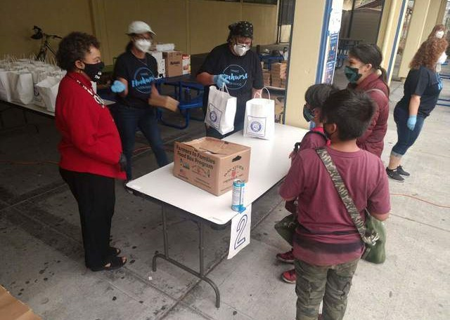 A family receiving grab and go food at Elmhurst United Middle School from staff and Oakland Rep. Barbara Lee (left) last September.