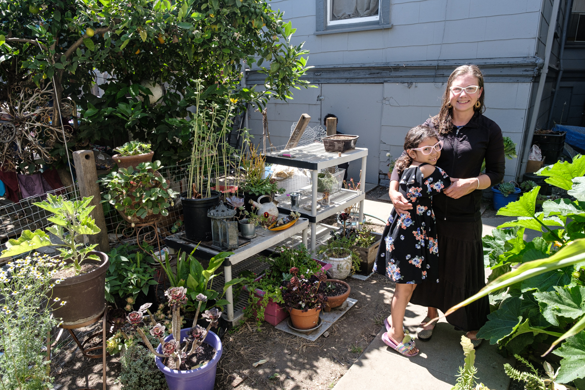 Young girl hugs a woman in a backyard overflowing with plants