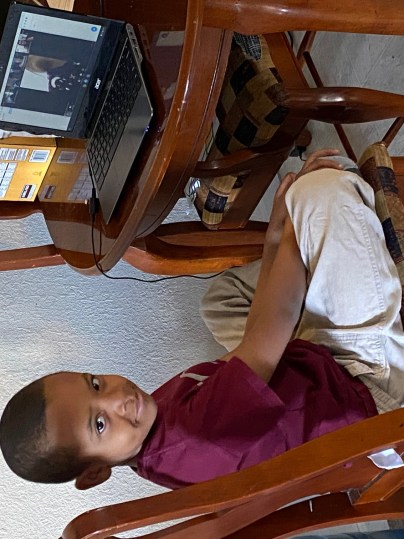 young boy sitting in front of computer