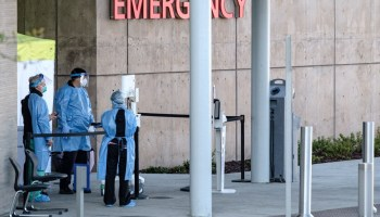 "staff in full safety gear stand under a sign that says ""emergency"""