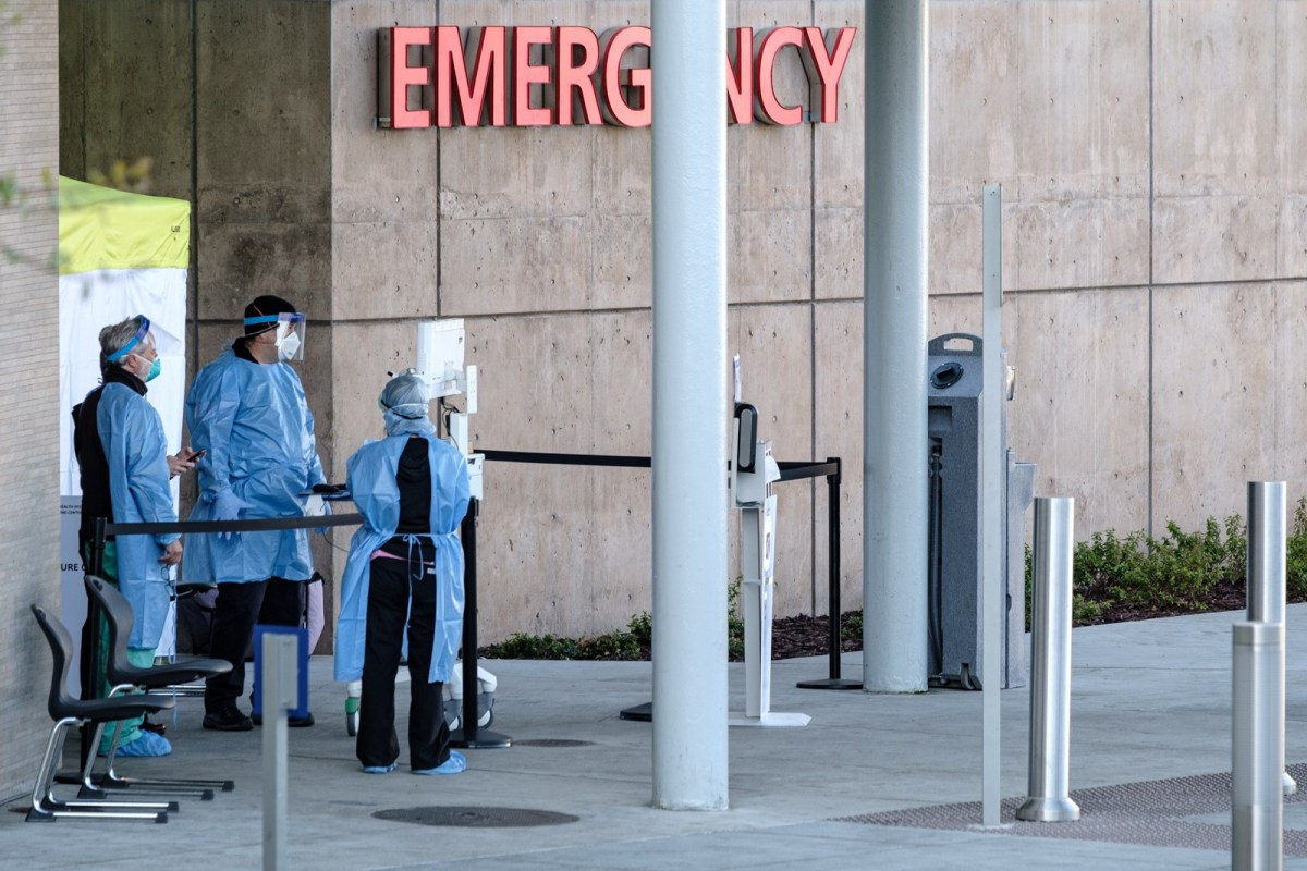 """staff in full safety gear stand under a sign that says """"emergency"""""""