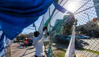 man pulls pieces of fabric off a fence. A tarp hangs overhead