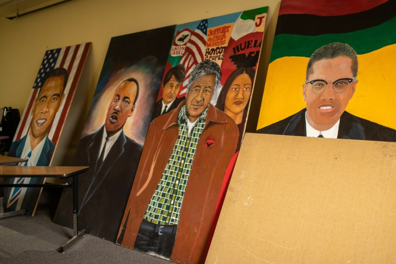 Large-scale paintings of Black and Brown leaders sit in storage of the high school.