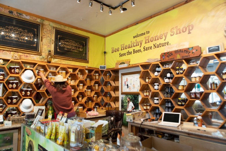 Jack, an employee at Bee Healthy Honey Shop fills inventory at the store.