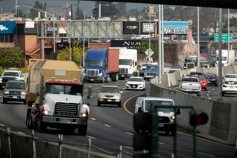 Semitrucks ride along Interstate 880 highway in East Oakland