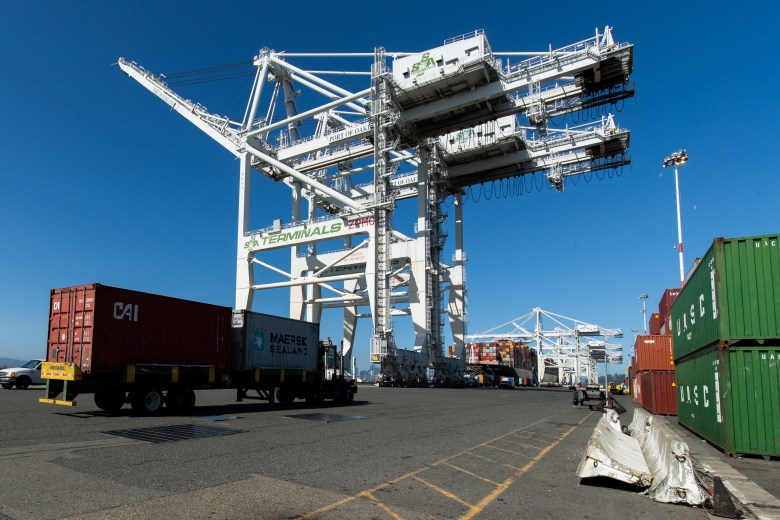 A big-rig truck hauls a shipping container at Howard Terminal.