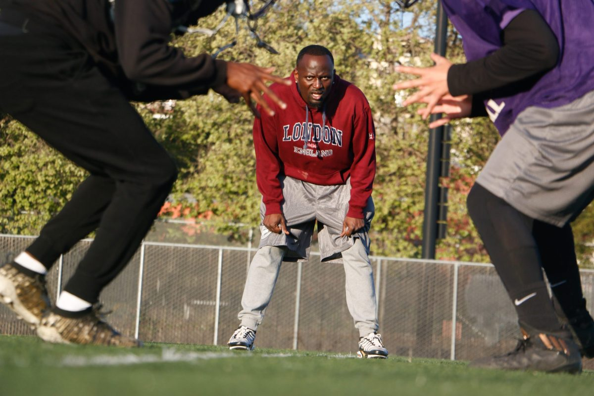 Castlemont High head football coach Ed Washington watches two of his players perform a drill during practice on April 15, 2021.