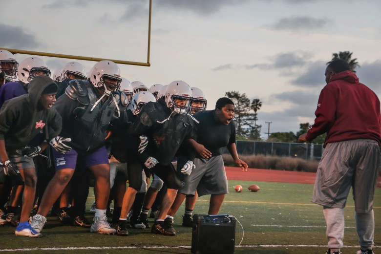 Castlemont High head football coach Ed Washington leads the team in a chant during practice on April 15, 2021.