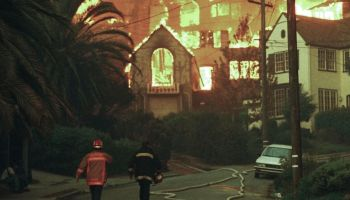 Firefighters walk up Rockridge Blvd. towards burning homes in Oakland, Calif., Oct. 20, 1991. A wind-driven brush fire exploded into a firestorm Sunday as it roared through residential neighborhoods in the hills above Oakland, engulfing hundreds of homes and killing 25 people. Credit: AP Photo/Olga Shalygin