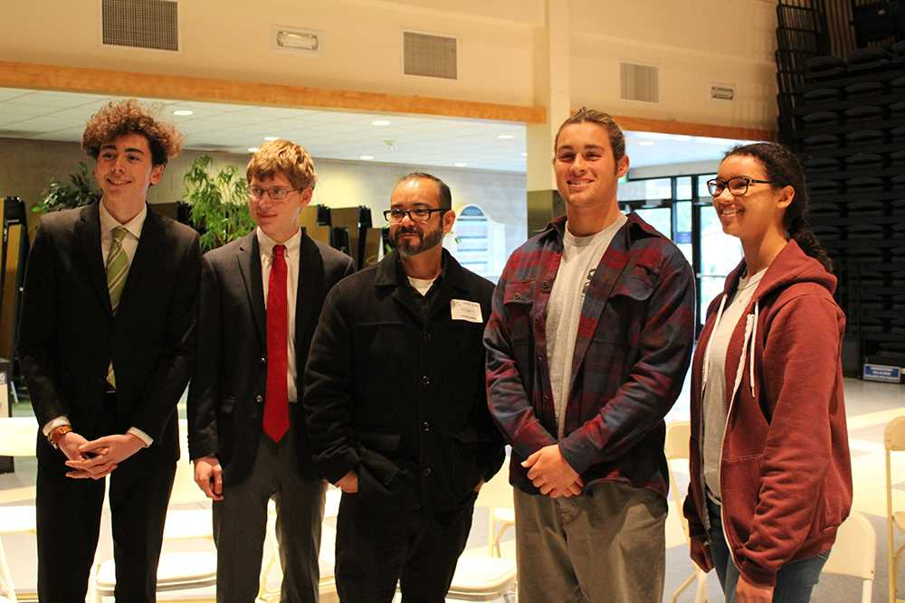 Competitors take picture with poet and coach Fernando Albert Salinas after the competition was complete. Senior Jacob Tennent was announced as winner and Senior Camille Polk as runner-up in the competition (Meghana Mudunuri/Talon).