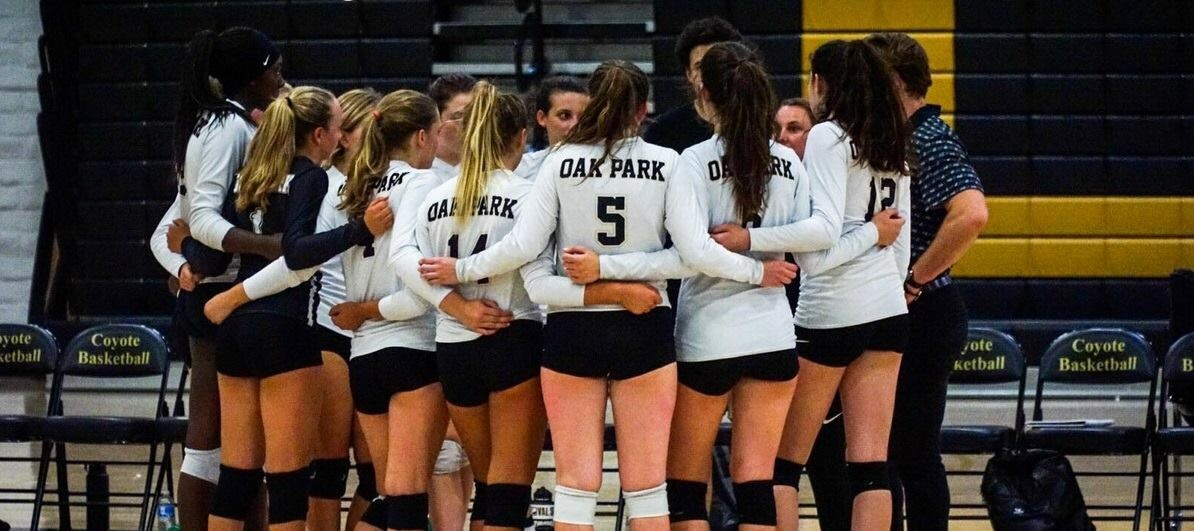 Oak Park High School's varsity volleyball team stands in a huddle