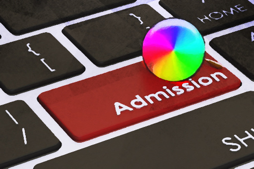 A rainbow pinwheel spins on top of a keyboard with the word admissions, representing the waiting period. Seniors had the option to submit early applications throughout October and November.