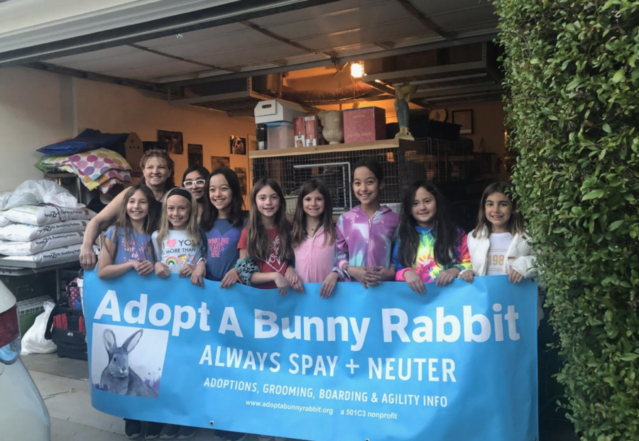 A fifth grade junior Girl Scouts troop stands behind a bunny rescue sign. The troop volunteered at the event and helped in the process of bunny adoptions. Image take before COVID.