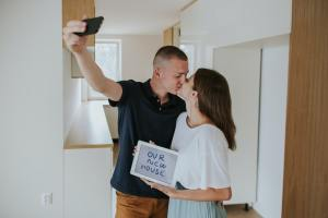 Young couple kissing and taking selfie in new house.