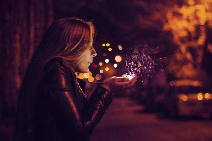 woman in dark street, blowing glitter off her hand as if to make a wish