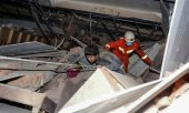 Homem é ajudado por bombeiro Foto: STR / AFP