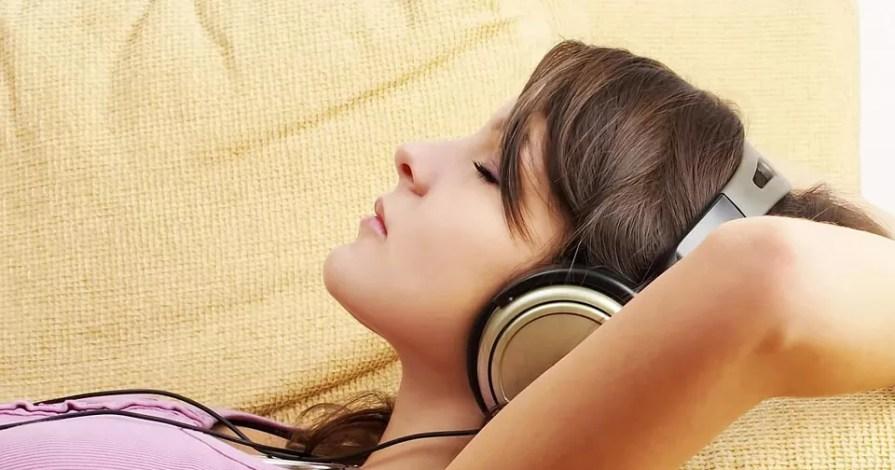 Uma mulher deitada no sofá de olhos fechados e com fone de ouvido