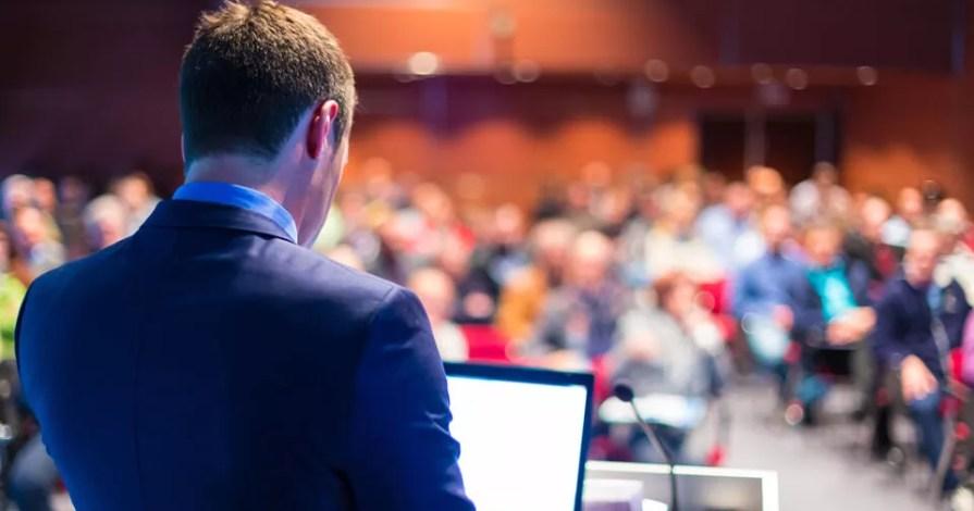 Um palestrante de terno em um púlpito; no púlpito há um notebook e um microfone. A plateia está em segundo plano desfocada