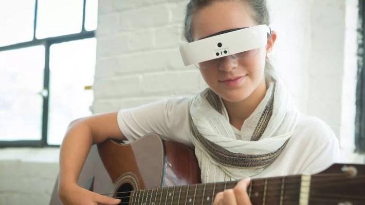 Uma mulher loira e sorridente, tocando violão enquanto usa o óculos eSight Glasses