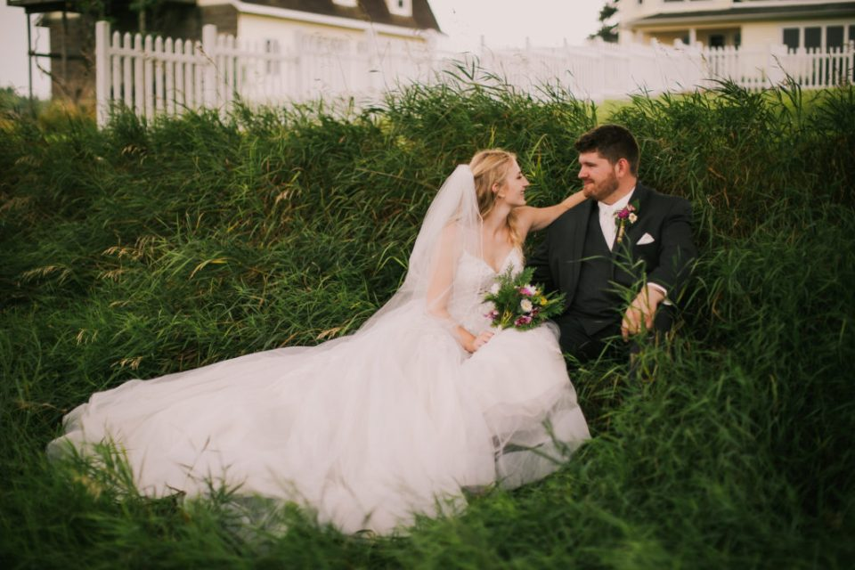 A bride and groom sit in the grass talking to each other