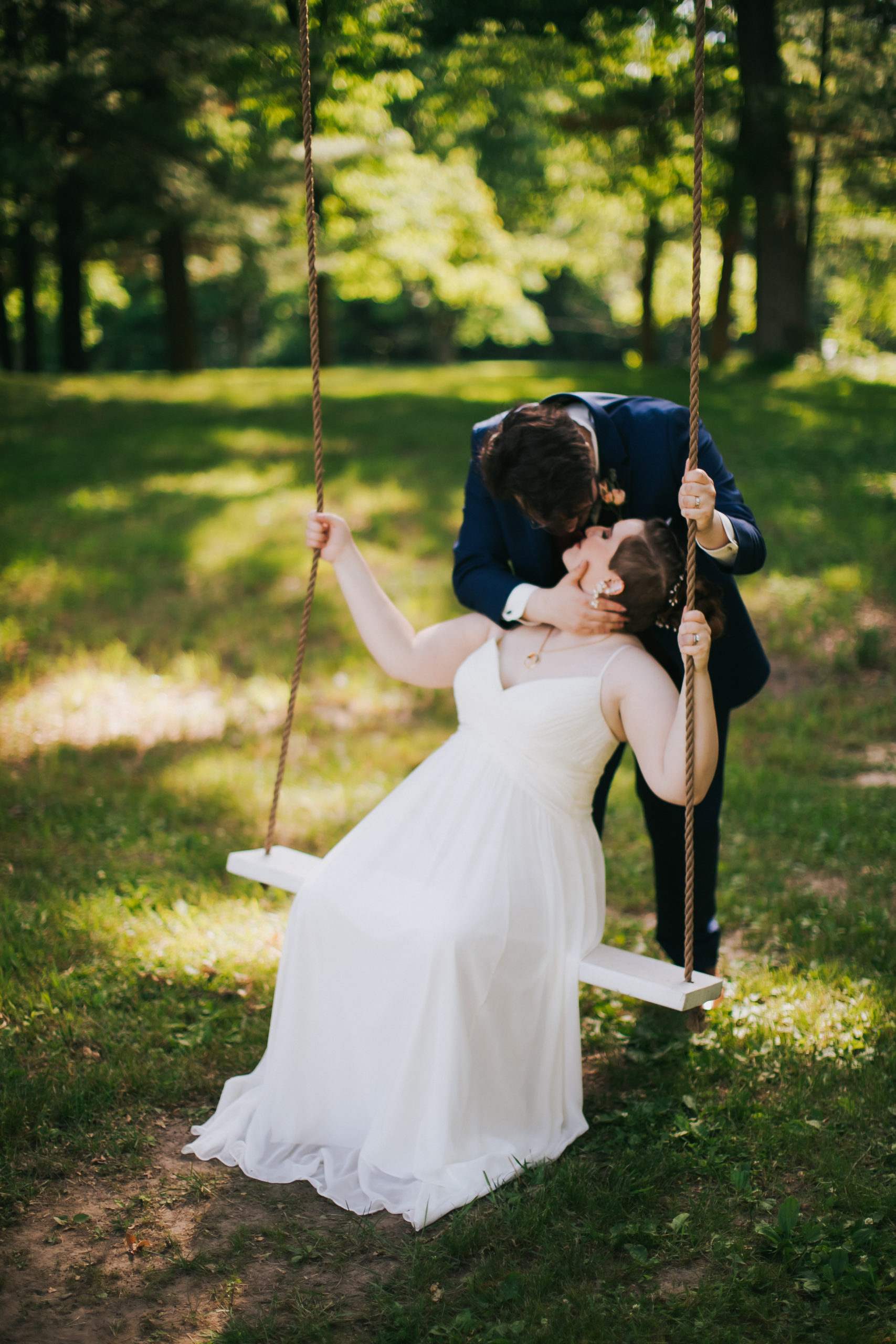 A man kisses his bride as she sits on a swing