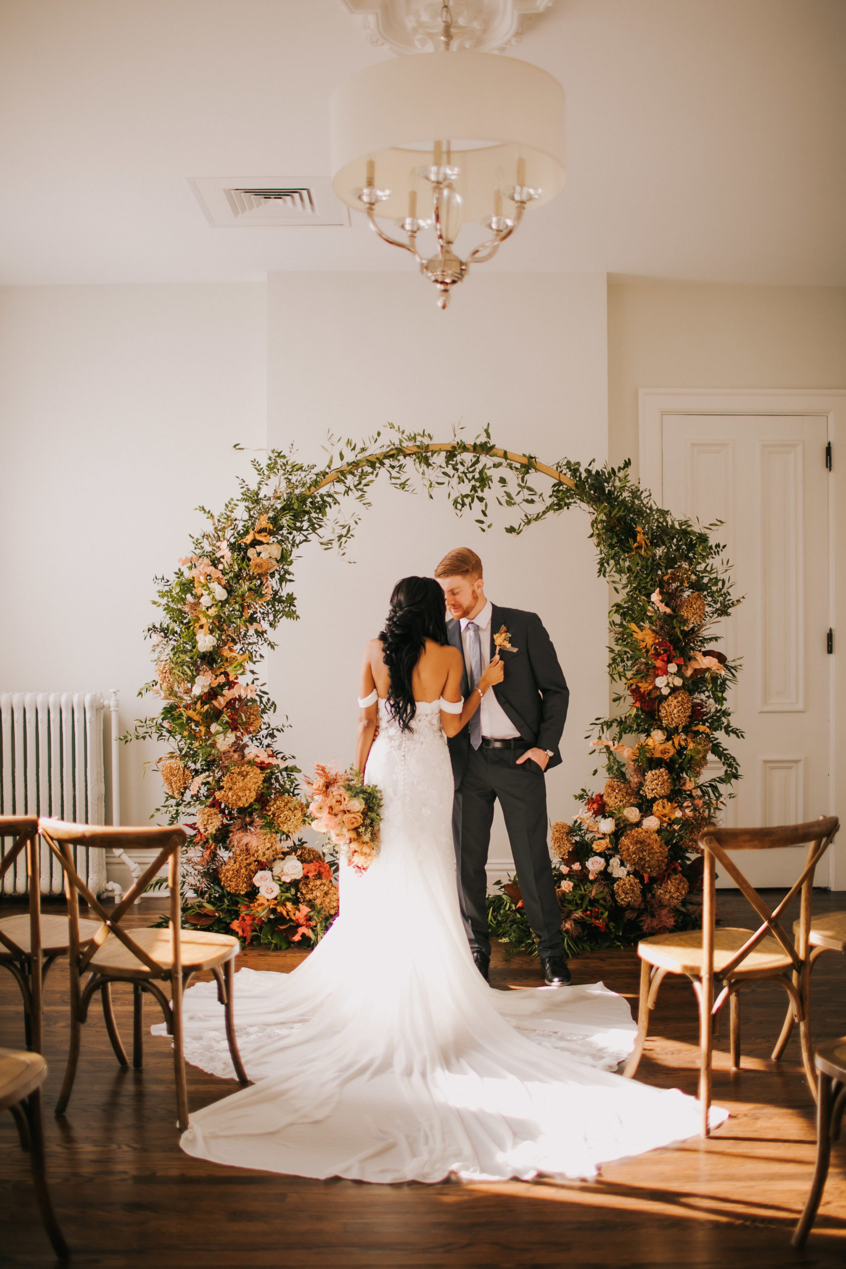 A man and woman stand under a flower arch at the Covenant at Murray Mansion